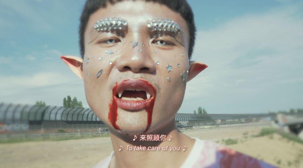 Eine Art futuristischer Vampir-Mensch schaut in die Camera. Still einer Videoarbeit von Yong Xiang Li.