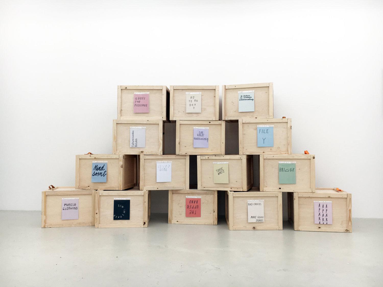 Holzboxen gestapelt vor einer weißen Wand.
