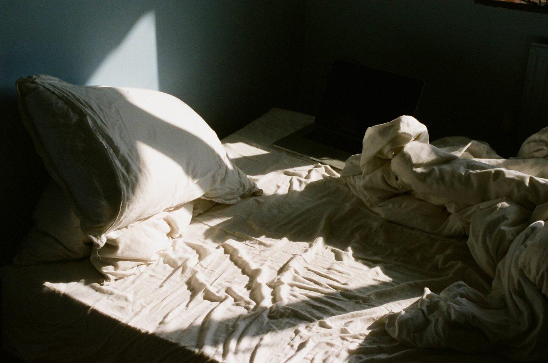 Licht fällt auf ein Bett mit zerknittertem Laken und Laptop.