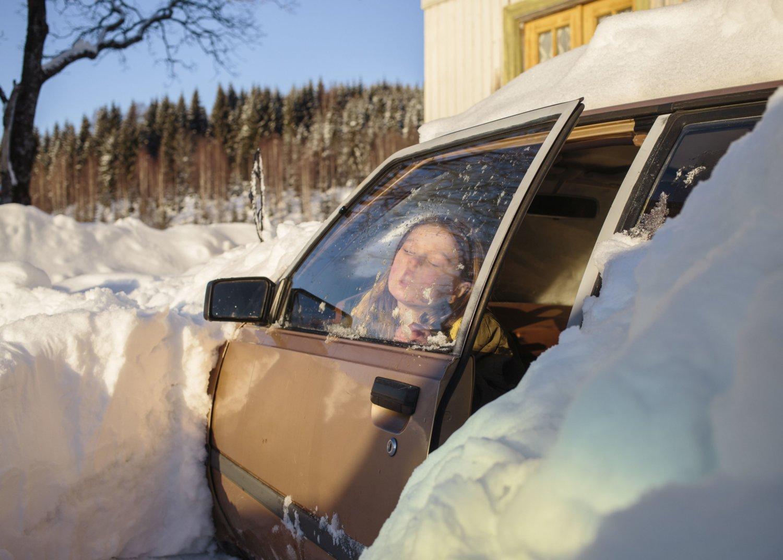 Ein Mädchen haucht an die Scheibe eines eingeschneiten Autos, Fotografie von Espen Eichhöfer.
