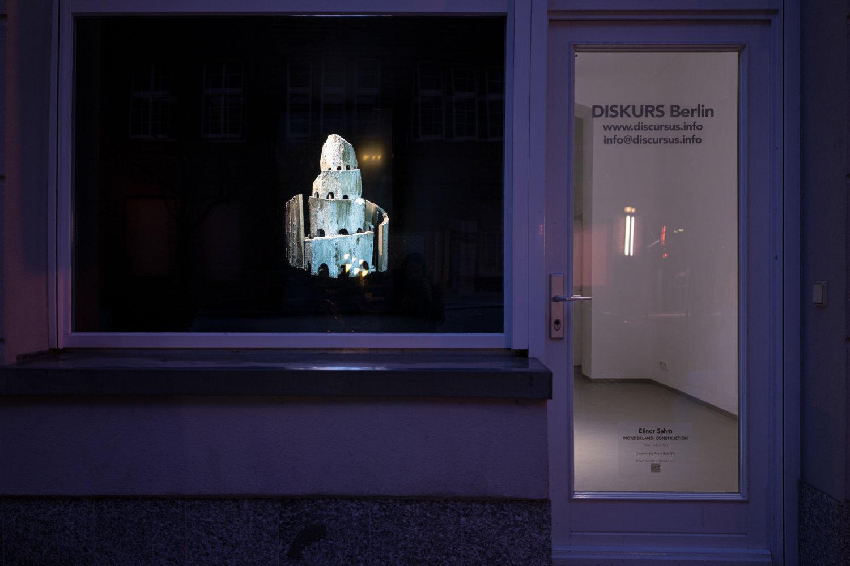 Schaufenster-Ausstellung bei Diskurs Berlin, links ein großes Fenster, wo ein Turm aus Beton zu sehen ist, rechts eine Tür, wo helles Licht erkennbar ist