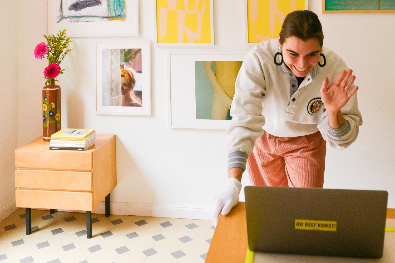 """Zu sehen ist die Gründerin der Galerie Kunst100, die in einen Laptop hinein winkt, auf dem steht auf einem Sticker """"Du bist Kunst!"""", im Hintergrund ist eine Bildergalerie zu sehen und ein Tisch mit Büchern und Blumen drauf"""