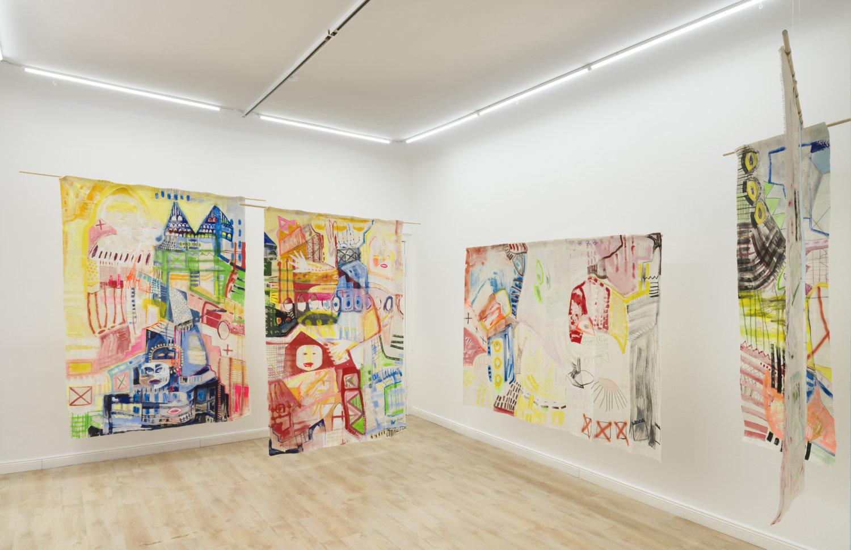 Ausstellungsansicht mit Arbeiten von Stella Meris in der Galerie Anahita Contemporary, zu sehen sind bunt bemalte Stoffe, die im weißen Raum hängen