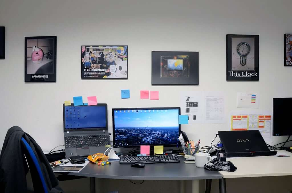 Zu sehen ist eine Installationsansicht von Good Job!. Man sieht einen Tisch mit einem Computerarbeitsplätze, an der Wand dahinter Kunst.