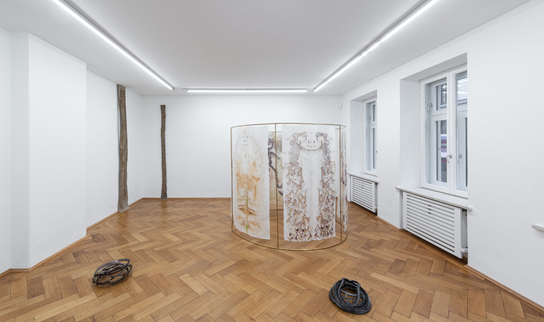 """Installationsansicht der Ausstellung """"On Survival"""". An der Wand zwei Skulpturen von Helene Appel, auf dem Boden zwei Fallen-artige Skulpturen von Hanna-Maria Hammari. Außerdem steht im Raum eine Skulptur mit Stoffbahnen von Chiara Camoni."""