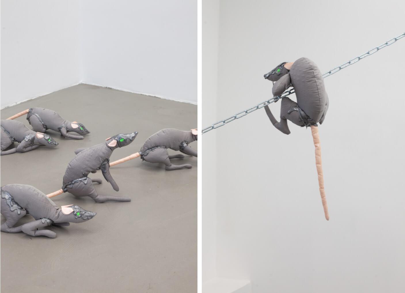 Mehrere Stofftier-Ratten mit grünen Augen klettern durch den Ausstellungsraum.