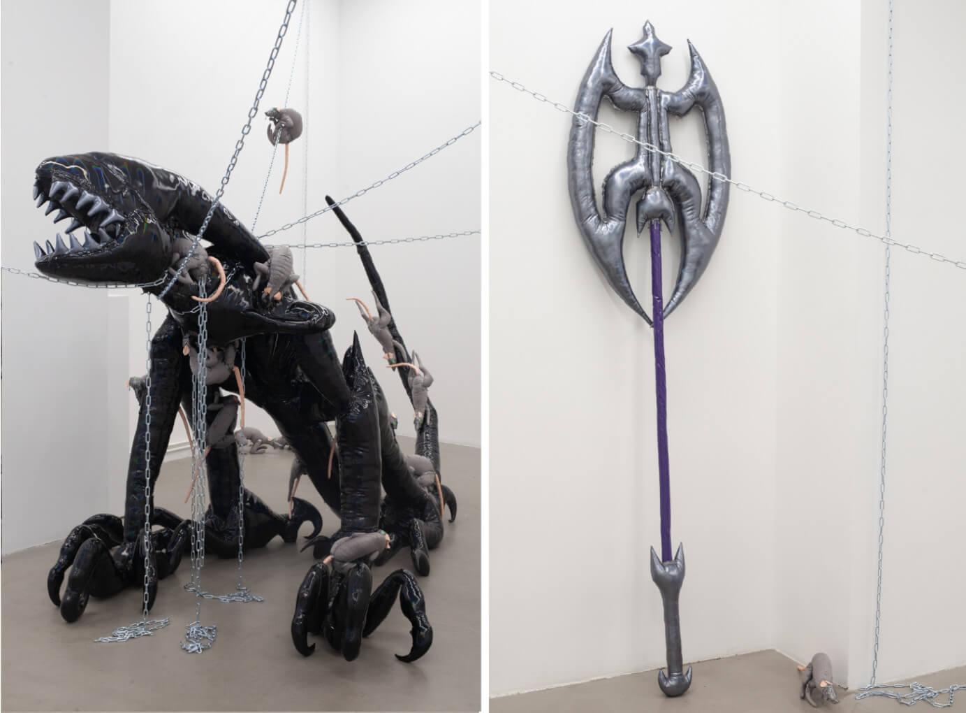 An der Wand lehnt eine Skulptur, die an eine Waffe erinnert. Links ist ein weiteres Mal das Stoff-Monster zu sehen.