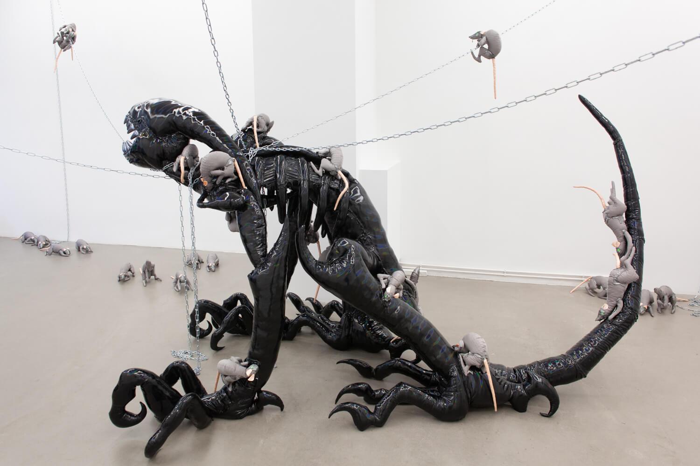 Die Installationsansicht zeigt die Skulptur einer schwarzen Kreatur, die von zahlreichen Stofftier-Ratten angefallen wird.