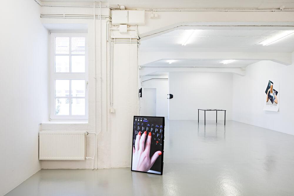 """Ausstellungsansicht im Paula Modersohn-Becker Museum in Bremen der Ausstellung """"Berührend"""", zu sehen ist die Videoarbeit """"Soft Nails"""" von Nadja Buttendorf, rote, weiche Fingernägel, die über eine Tastatur streichen"""