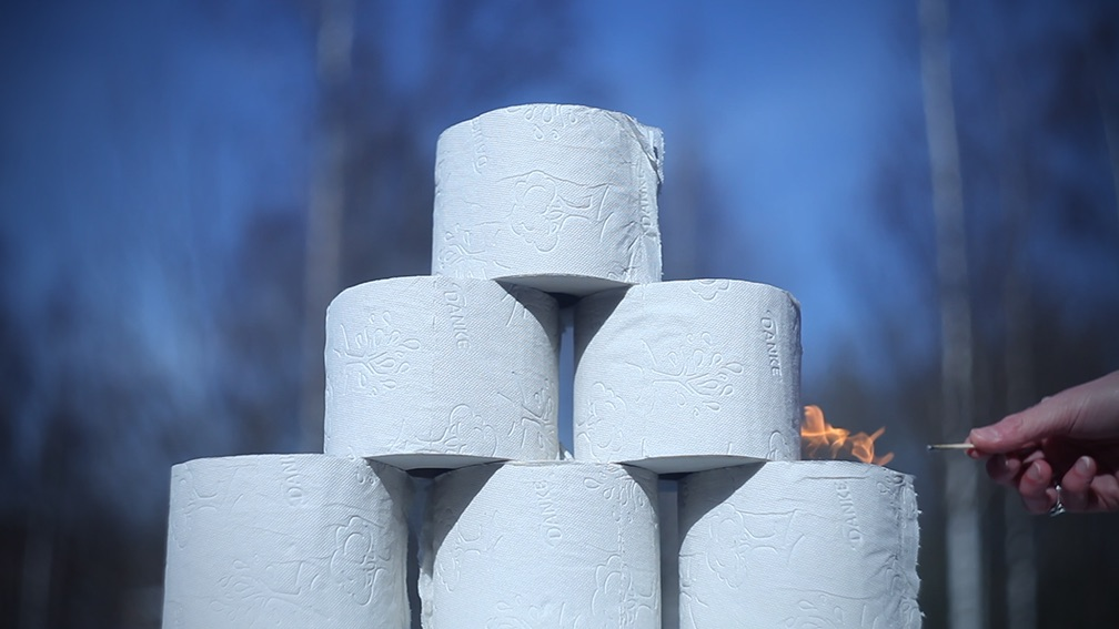 Sechs aufgetürmte Klorollen werden mit einem Streichholz in Brand gesetzt.