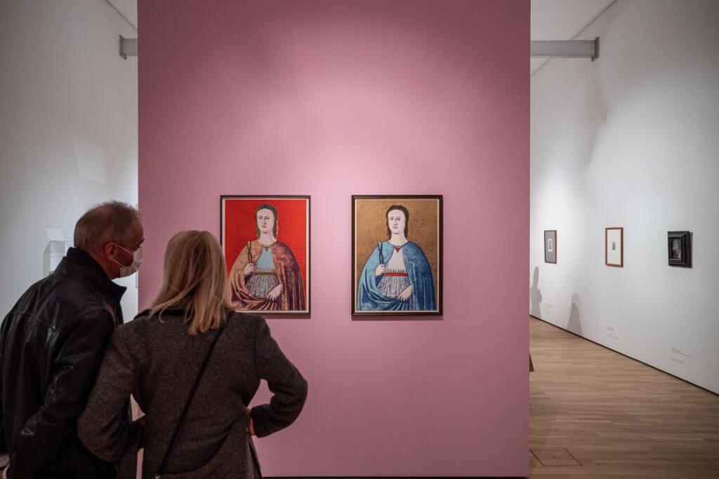 """Ausstellungsansicht """"In aller Munde"""" im Kunstmuseum Wolfsurg, zwei Besucher:innen stehen vor zwei Bildern von Andy Warhol, die Bilder hängen an einer rosafarbenen Wand"""