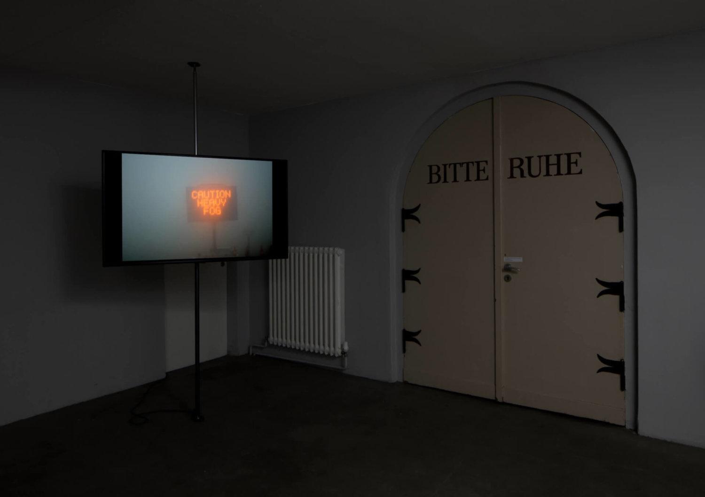 Zu sehen ist ein Raum der Galerie Ebensperger, eine Tür, auf der Bitte Ruhe steht und links daneben ist ein Bildschirm, auf dem eine Arbeit von Benjamin Heisenberg zu sehen ist, der Bildschirm zeigt ein Filmstill und zu sehen ist ein Leuchtschild, auf dem Caution Heavy Fog steht, der Rest ist neblig
