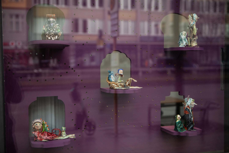 Durch eine Glasscheibe sind Keramikfiguren von Emily Hunt zu sehen, es sind merkwürdige und schräge Gestalten in verschiedenen Posen und Haltungen