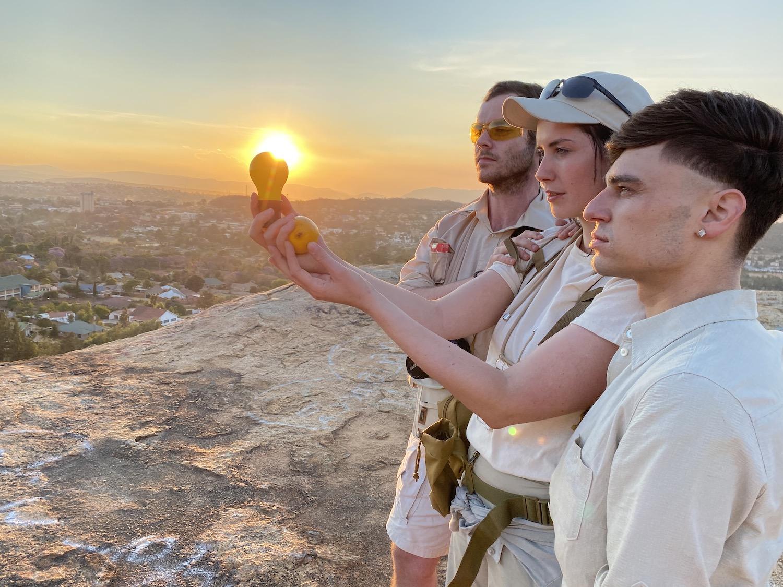 """Drei Mitglieder der Frankfurter Hauptschule halten die """"Capri Batterie"""" vor die untergehende Sonne."""