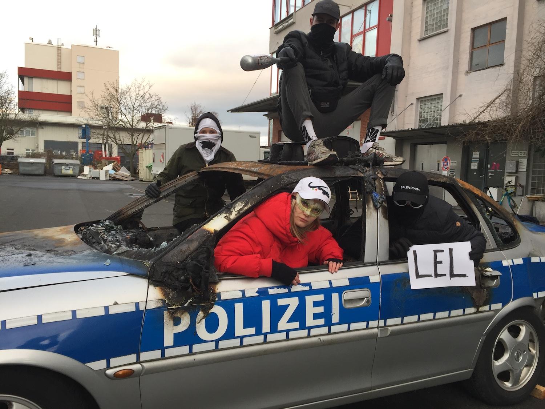 """Die Frankfurter Hauptschule posiert mit einem ausgebrannten Polizeiauto. Ein Mitglied der Gruppe hält einen Zettel mit der Aufschrift """"lel""""."""