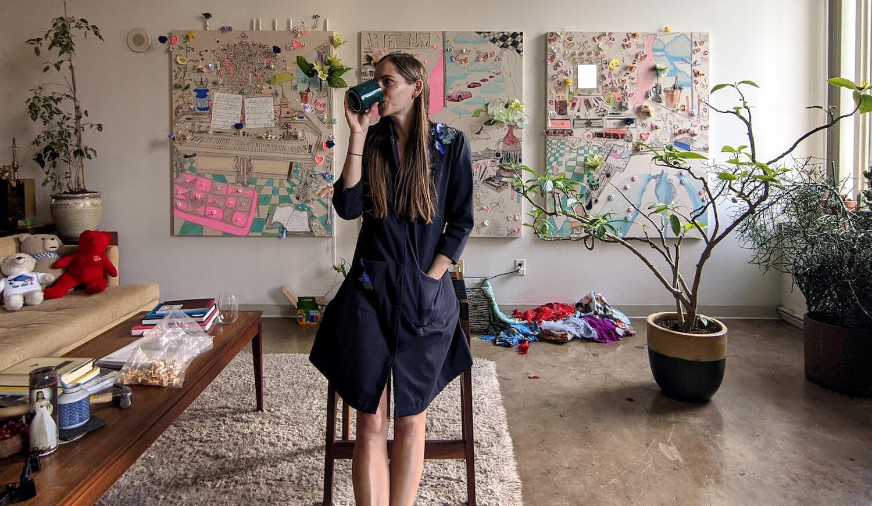 Die Künstlerin Gretchen Andrew lehnt an einem Hocker und trinkt aus einer Tasse. Im Hintergrund drei ihrer Vision Boards.