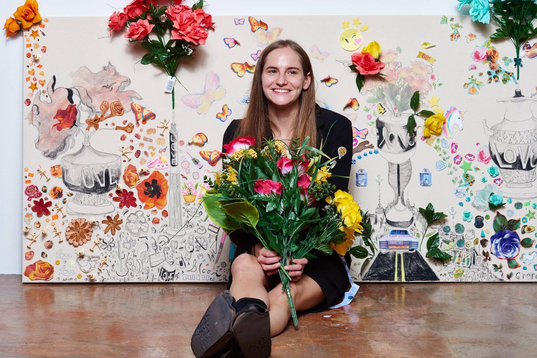 Die Künstlerin Gretchen Andrew sitzt lachend mit einem Strauß Plastikblumen in der Hand vor einem ihrer Vision Boards.