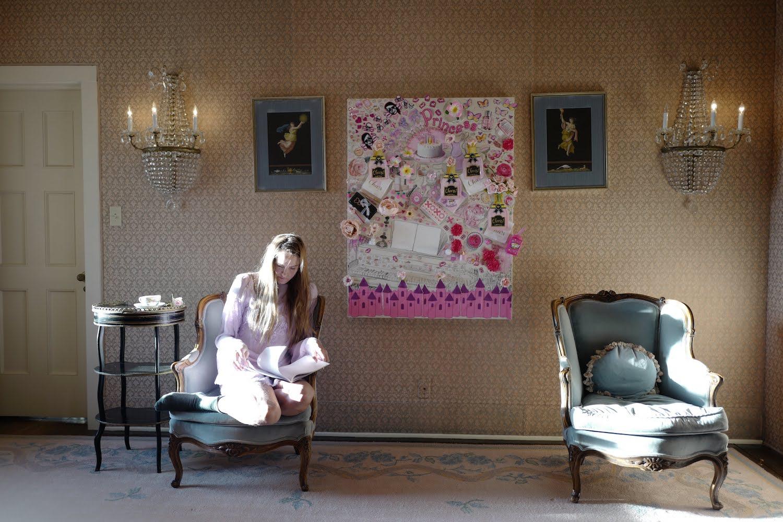 Gretchen Andrew sitzt auf einem antiken Sessel und scheint zu lesen. Der Raum ist glamourös eingerichtet, an der Wand hängt eine ihrer Arbeiten.
