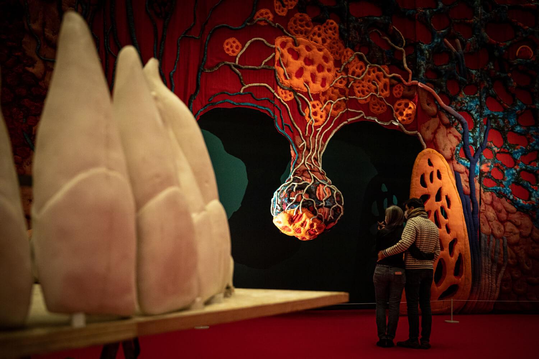 """Ausstellungsansicht """"In aller Munde"""" im Kunstmuseum Wolfsburg, links im Vordergrund sind große Zähne zu sehen und im Hintergrund eine große Mundhöhle vor der ein sich umarmendes Paar steht"""