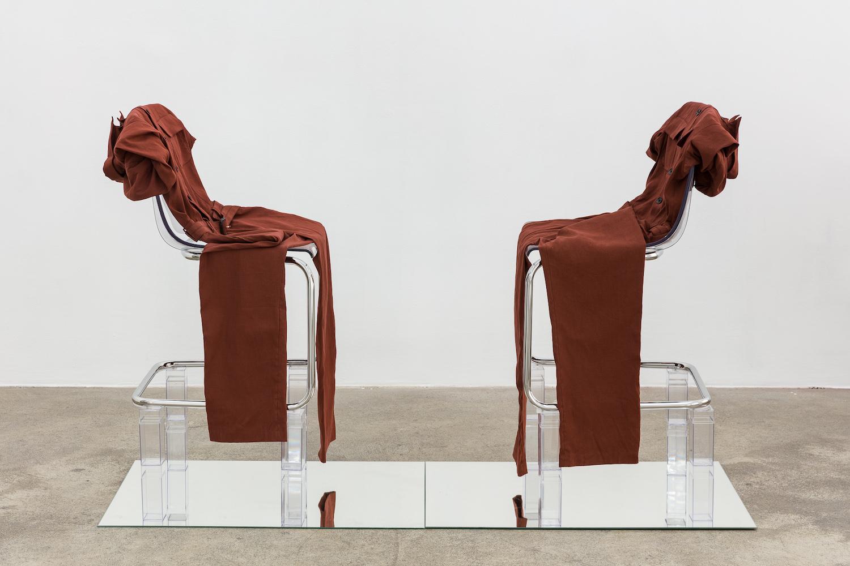Skulptur von Kayode Ojo. Zwei Stühle stehen sich auf einer Spiegelfläche gegenüber, beide mit identischen Kleidungsstücken in Rostrot bedeckt.