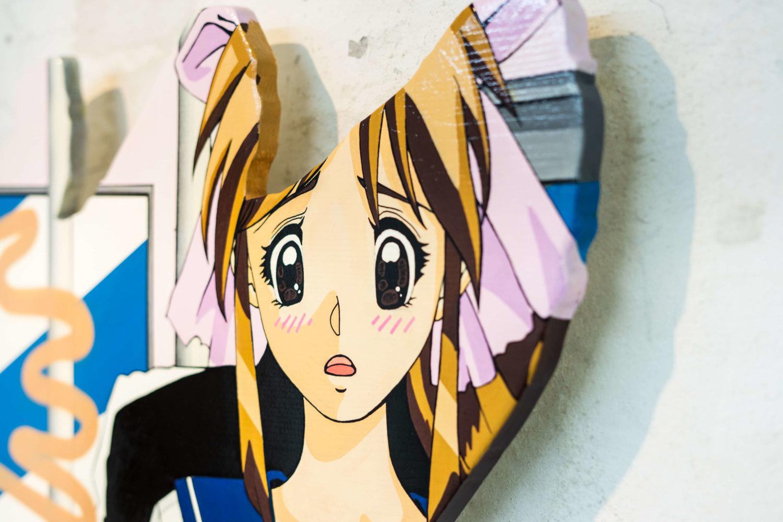 Auf einer ausgesägten Holzplatte ist das erschrockene Gesicht einer Anime-Figur mit weit aufgerissenen Augen zu sehen.
