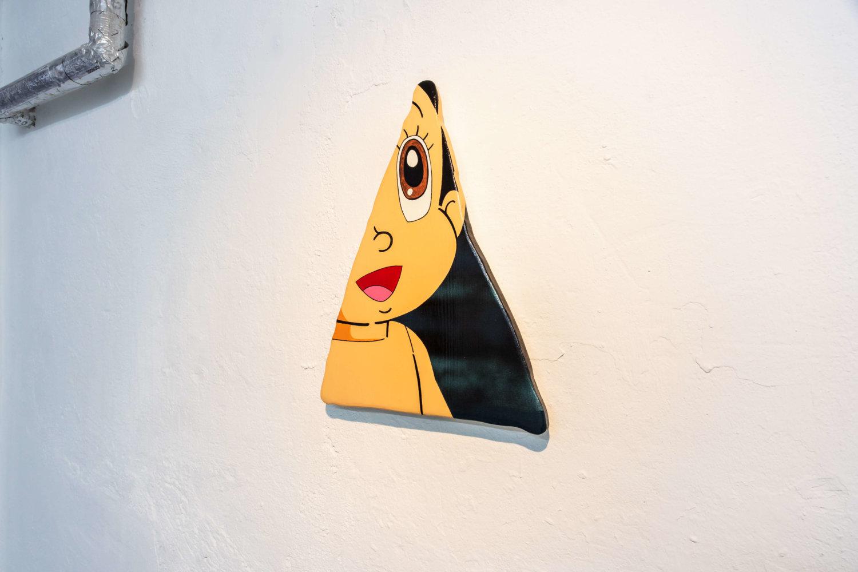 Auf einer dreieckig ausgesägten Holzplatte ist das Gesicht der Figur Astro Boy mit weit aufgerissenen Augen zu sehen.
