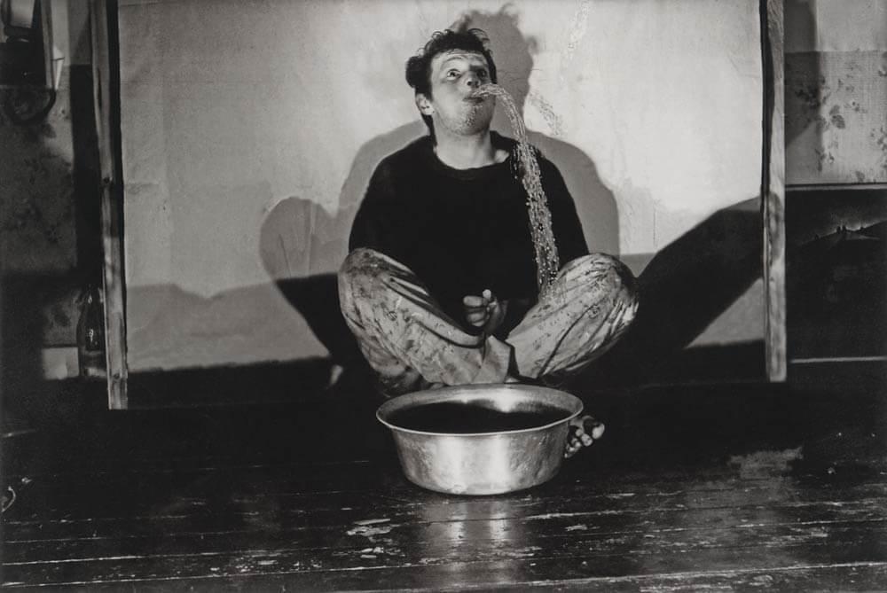 Ein Schwarz-Weiß-Bild auf dem ein speiender Mann zu sehen ist, der Wasser in eine Schüssel spuckt