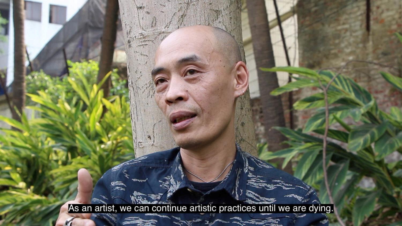 "Filmstill bei dem Huang Xiaopeng zu sehen ist mit dem Untertitel ""As an artist, we can continue artistic practices until we are dying"""