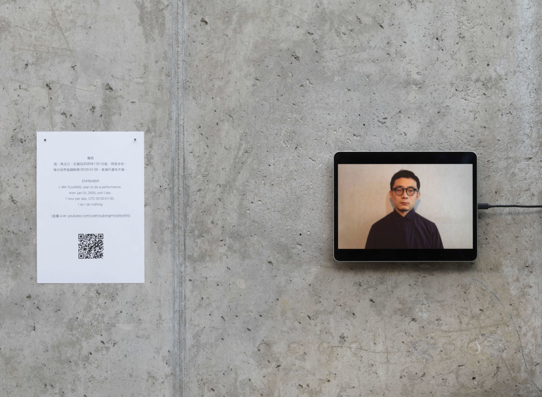 Eine graue Wand, an der ein Tablet hängt, zu sehen ist ein Mann, der stumm und bewegungslos da steht, Blick nach vorne gerichtet