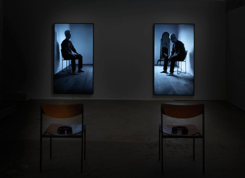 Ein dunkler Raum mit zwei Stühlen und zwei Bildschirmen im Hochformat, auf denen jeweils eine zwielichtige Situation zu sehen ist, je ein Mann sitzt im Bild auf einem Stuhl, rechts ist noch ein Spiegel im Hintergrund zu sehen, der ebenfalls eine Person zeigt
