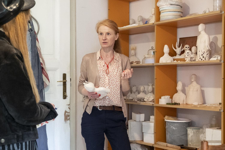 Künstlerin Anna Mars in ihrem Atelier im Gespräch mit Gallerytalk, sie steht vor einem Regal, in dem sie noch unfertige Arbeiten lagert