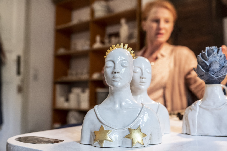 Ein weiblicher Keramik-Kopf im Vordergrund von der Künstlerin Anna Mars, im Hintergrund verschwommen sie selbst