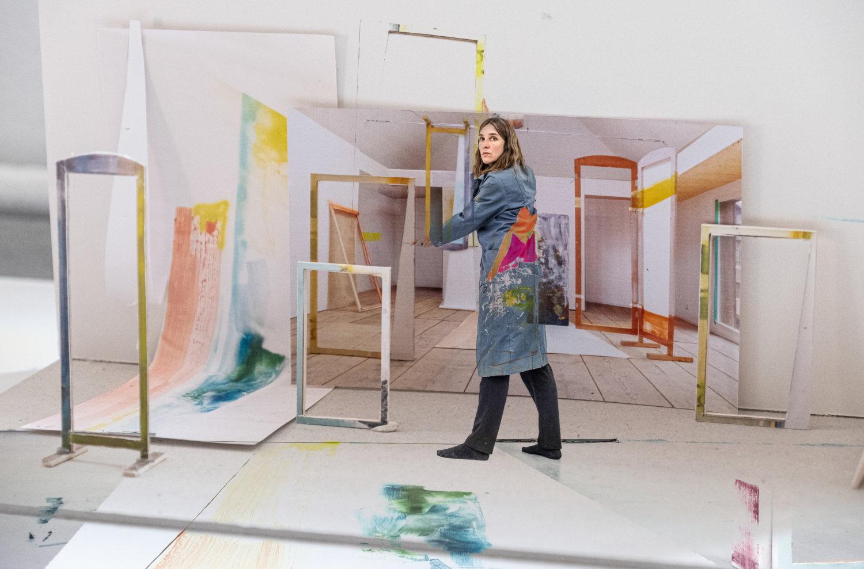Die Künstlerin Heike Gallmeier steht in ihrer Installation und hält einen Rahmen in den Händen, um sie herum stehen andere Rahmen und sie steht vor einer großen Fotografie