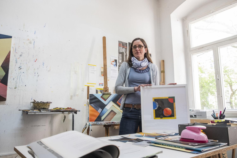 Künstlerin Ines Doleschal in ihrem Atelier, sie hält ein gerahmtes Werk in den Händen, im Hintergrund steht eine weitere Arbeit auf einer Staffelei