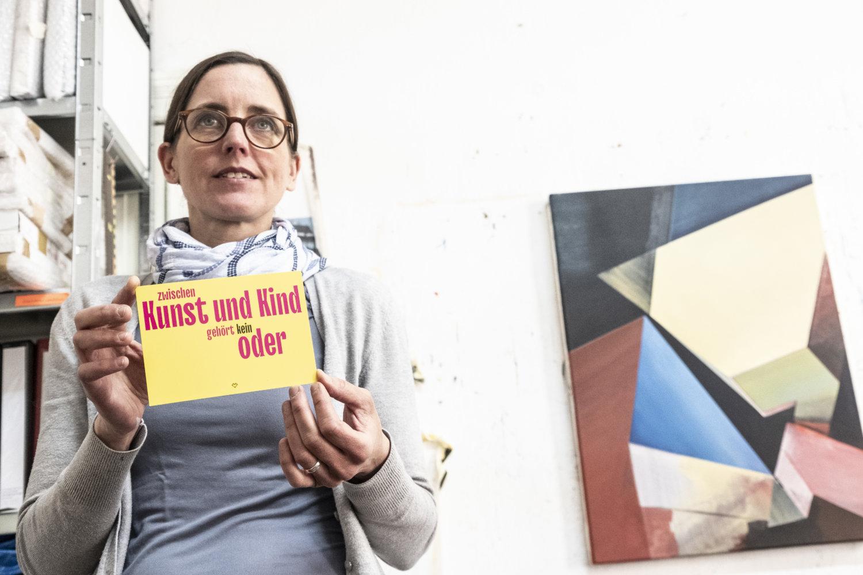 """Künstlerin Ines Doleschal in ihrem Atelier, sie hält eine Karte in den Händen auf der steht """"zwischen Kunst und Kind gehört kein Oder"""""""