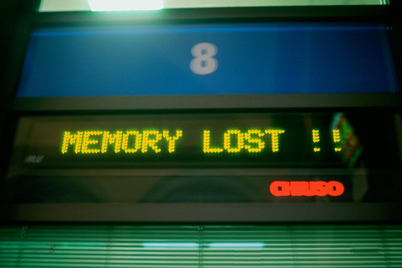 Eine digitale Anzeige, auf der in gelben Großbuchstaben MEMORY LOST mit zwei Ausrufezeichen steht, darüber ein blaues Schild mit einer weißen 8