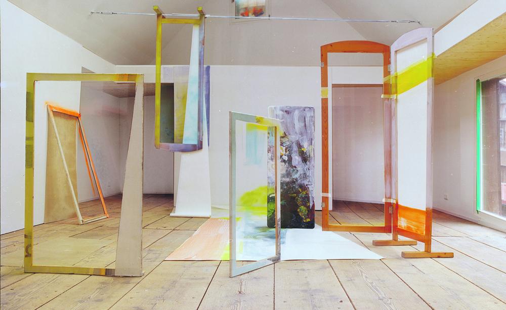 Atelieransicht von Heike Gallmeier, zu sehen ist eine große Rauminstallation mit verschiedenfarbigen Rahmen, die verschieden angeordnet sind