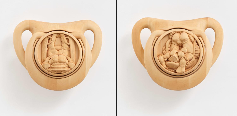 Zwei hölzerne Skulpturen der Künstlerin Anna Uddenberg stellen zwei überdimensionale Schnuller dar, in denen muskulöse Körper in Babykleidung geschnitzt sind.
