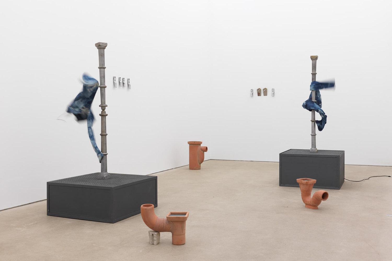 """Ausstellungsansicht der Ausstellung """"Super Call Me Fragile Ego"""" von Sofia Hultén. An zwei mastähnlichen Skulpturen sind Jeanshosen befestigt, die durch ein Gebläse herum wehen."""