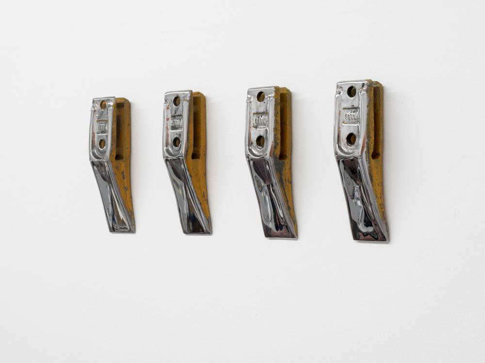 Vier Zähne eines Baggers wurden an die Wand geschraubt und poliert. Sie glänzen und lassen sich kaum ihrer ursprünglichen Funktion zuordnen.