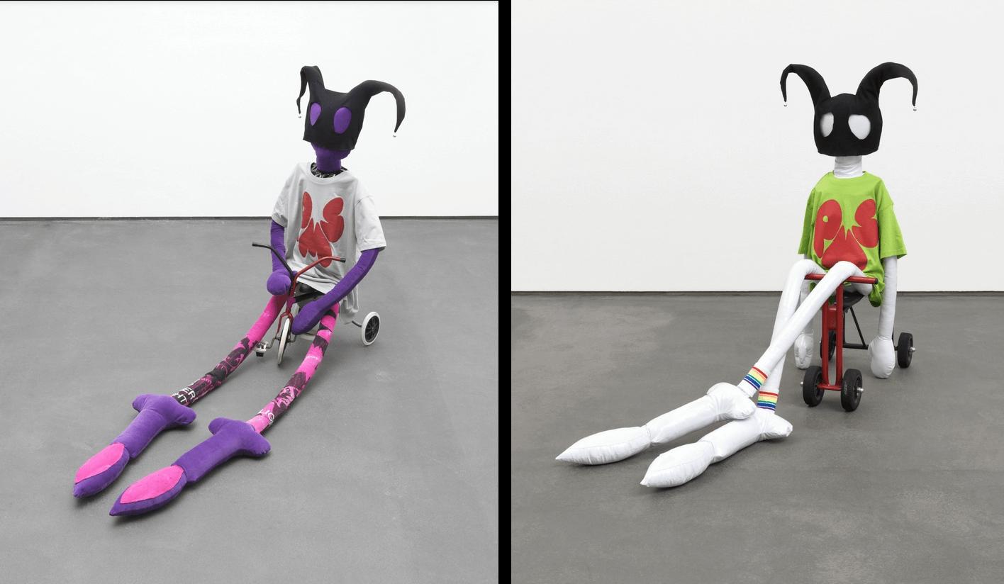 """Zwei der so genannten """"Soft Heroes"""", lebensgroße Puppen aus unterschiedlichen Materialien, sitzen auf Dreirädern. Ihre langen Gliedmaßen hängen auf den Boden."""