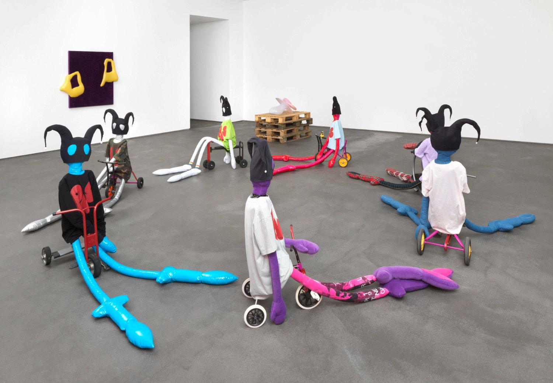 Im Vordergrund sitzen sieben Puppen mit langen Gliedmaßen auf Dreirädern, die im Kreis aufgestellt sind. Im Hintergrund sind weitere Werke von Thomas Liu Le Lann zu sehen.