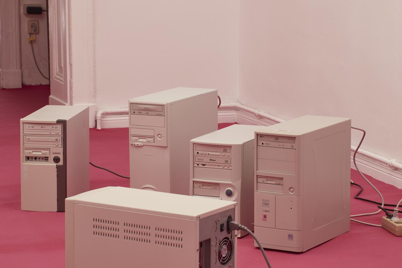 Fünf alte Computer-Tower auf pinkfarbenem Teppichboden.