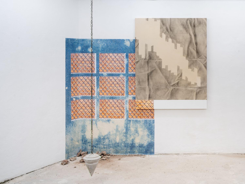 Installation von Sabrina Podemski aus zwei Gemälden und einem von der Decke hängenden Pendel.