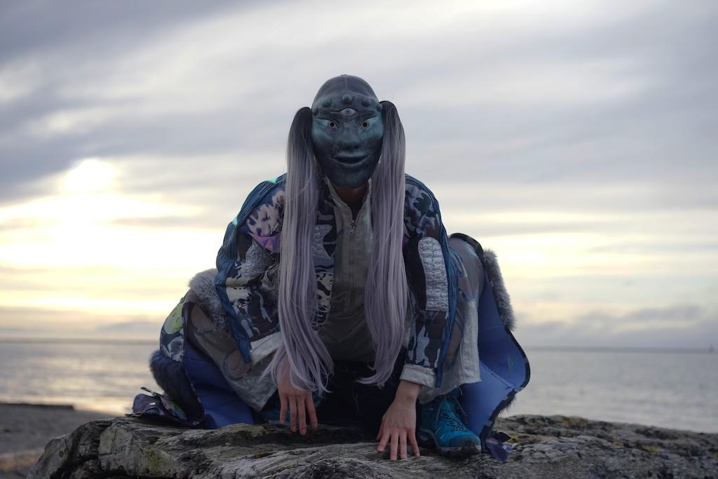 Portrait von Zadie Xa mit Maske auf einem Fels