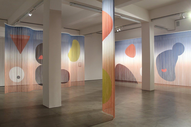 Hinter und zwischen zwei Stützpfeilern innerhalb des Ausstellungsraumes lassen sich drei bunte Vorhänge ausmachen, die von zielgerichteten Spots angestrahlt werden.