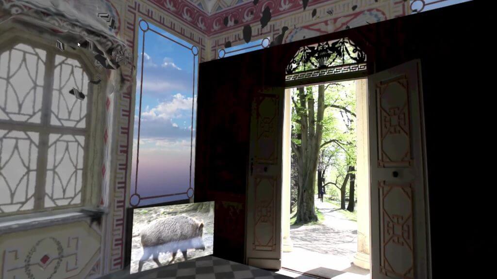 Die Innenansicht eines Raumes ist zu sehen, auf einem Bildschirm rennt ein Wildschwein. Der Blick nach draußen lässt ein paar Bäume erkennen.