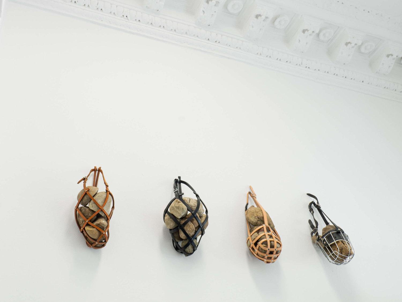 Vier Maulkörbe hängen an der Wand und sind mit großen Steinen gefüllt.