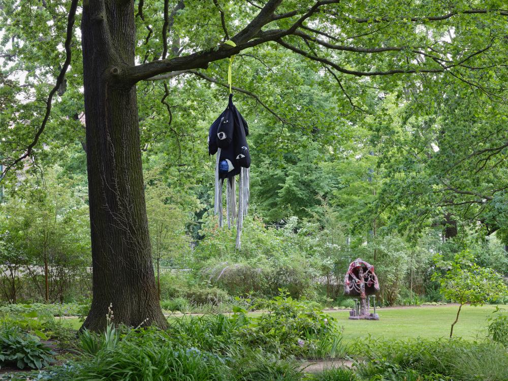 """An einer Eiche hängt Hoda Tawakols Arbeit """"LURE #22"""", die an einen riesigen Köder erinnert. Im Hintergrund ist Tom Volkaerts Skulptur eines gigantischen Pilzes zu sehen."""