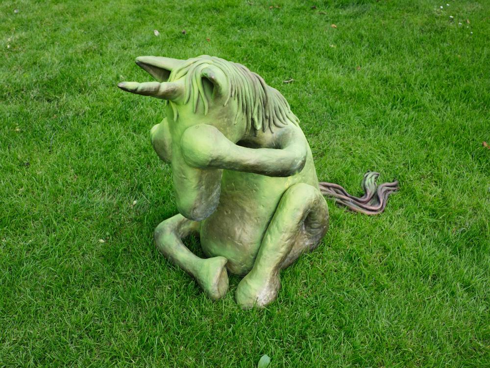 Auf einer Wiese sitzt eine Einhorn-Skulptur, die sich die Augen zuhält. Eine Arbeit von Jenny Brosinski.